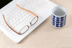 Eyeglasses on laptop with  an empty cup of tea. Royalty Free Stock Photo