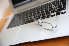 Eyeglasses on laptop keyboard. Closeup of laptop keyboard and eyeglasses Stock Photography