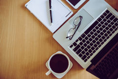 Eyeglasses on laptop keyboard pen on notebook with coffee cup Royalty Free Stock Image