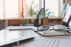 Eyeglasses on laptop keyboard on wooden table Stock Images