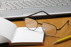 Eyeglasses,laptop and notebook. Stock Photos