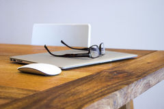 Eyeglasses on laptop in office. Office still life of wooden desk with closed laptop, computer mouse and eyeglasses Royalty Free Stock Photos