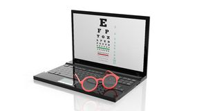Eyeglasses on laptops keyboard with eyesight test on screen Royalty Free Stock Photography