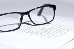 Eyeglasses lie on the book Stock Photos