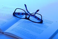 Eyeglasses lie on the book Stock Photography