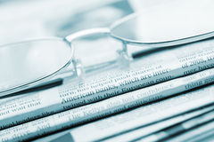 Eyeglasses lie on a pile of newspapers.Blue toned Stock Images
