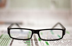 Eyeglasses lying around newspapers Royalty Free Stock Photography