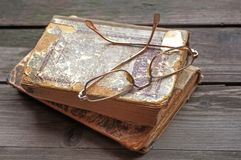 Eyeglasses lying on shabby battered old book lying on the old cr royalty free stock photos