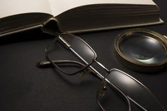 Eyeglasses with magnifying glass on dark surface with books. High resolution image design for Ophthalmologist concept Stock Photography