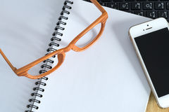Eyeglasses mobilephone and a notebook on laptop computer Royalty Free Stock Photo