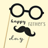 Eyeglasses, mustache and text happy fathers day. The text happy fathers day and a pair of round-framed eyeglasses and a mustache attached to handles depicting a stock images