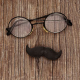 Eyeglasses and mustache on a wooden surface Royalty Free Stock Image