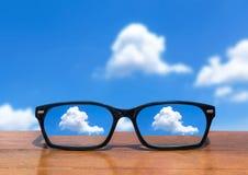 Eyeglasses na drewnianym stołu przodzie abstrakcjonistyczne białe chmury Fotografia Stock