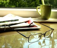 The eyeglasses, the newspaper on the table and the. Green cup Royalty Free Stock Photos