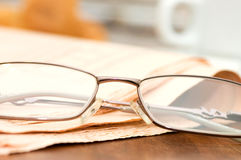 Eyeglasses on the newspaper on a wooden table Royalty Free Stock Photo