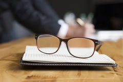 Eyeglasses on notebook with background of businessman working wi Stock Image