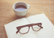 Eyeglasses on notebook and black coffee Royalty Free Stock Images