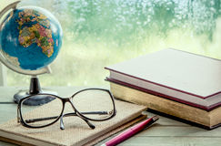 Eyeglasses on notebook with book  and globe Stock Image