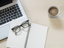 Eyeglasses on notebook, laptop computer and a cup of hot coffee Royalty Free Stock Images