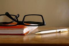 Eyeglasses, notebook and a pen Stock Photography