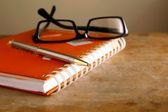 Eyeglasses, notebook and a pen Royalty Free Stock Image