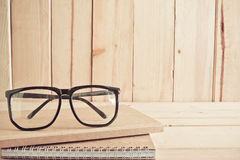 Eyeglasses and notebook on wooden table over wood background Stock Photos
