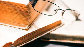 Eyeglasses on old book stack Royalty Free Stock Photo