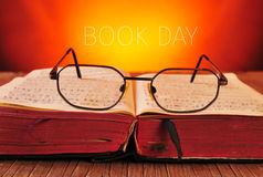 Eyeglasses, old book and the text book day Stock Photos