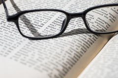 Eyeglasses on an old open book. Black eyeglasses on an old open book. French novel Stock Photo