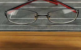 Eyeglasses on the old thick book Royalty Free Stock Photo