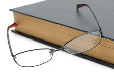 Eyeglasses on the old thick book Stock Image