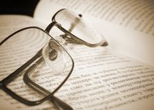 Eyeglasses on the old thick book. Royalty Free Stock Photos