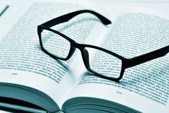 Eyeglasses on an open book, in duotone Stock Image