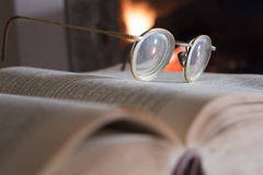 Eyeglasses, open book and fireplace stock photo