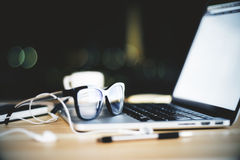 Eyeglasses on opened laptop with blank screen and headphones and Stock Image