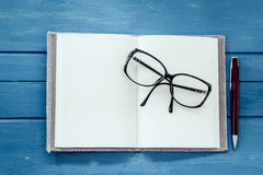 Eyeglasses on opened notebook with pen Royalty Free Stock Photography
