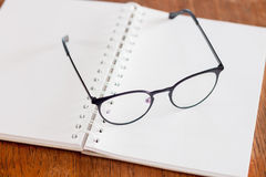 Eyeglasses on opened spiral notebook Royalty Free Stock Images