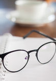 Eyeglasses on opened spiral notebook Stock Image
