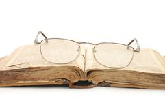 Eyeglasses over open book. Isolated white Royalty Free Stock Image