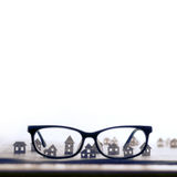 Eyeglasses  with paper houses. Royalty Free Stock Images
