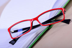 Eyeglasses and paper notebook Stock Photography