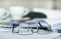 Eyeglasses and papers. Picture of eyeglasses and blank papers on the table Stock Images