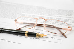 Eyeglasses and pen Stock Photos