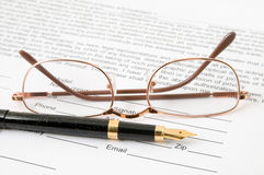 Eyeglasses and pen. Lay on the document Stock Image