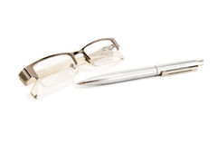 Eyeglasses and pen Stock Images