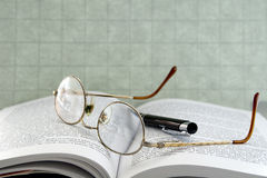 Eyeglasses with pen. Nice eyeglasses on top of an open book with a pen Stock Images