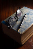Eyeglasses and pen on antique book. Royalty Free Stock Images