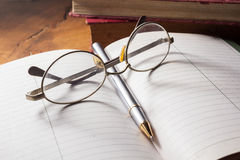 Eyeglasses and pen on book. Stock Images
