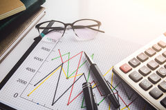 Eyeglasses and pen on financial document with data Royalty Free Stock Photo