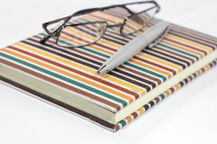 Eyeglasses and pen on notebook Royalty Free Stock Photo